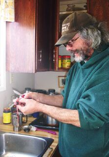 Wayne guts the whitefish he caught the day before and examines the stomach contents to see what the fish have been eating